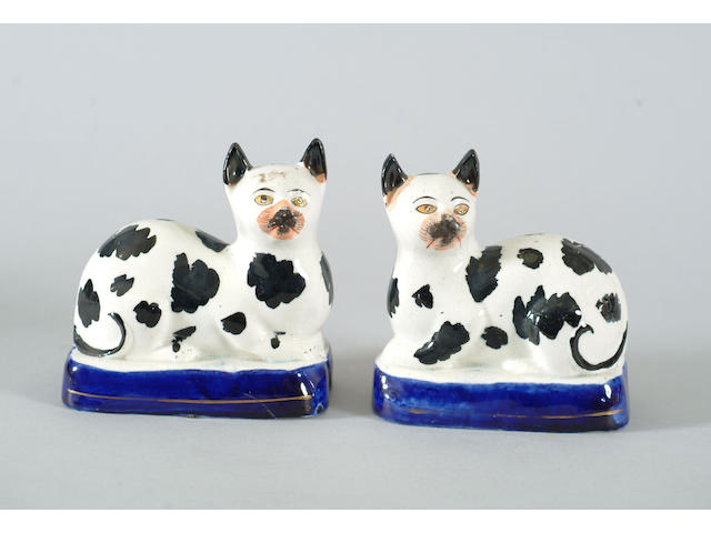 A pair of Staffordshire models of recumbent cats and another similar. (3)