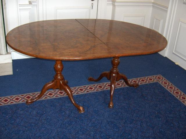 A George III style burr walnut twin pedestal dining table
