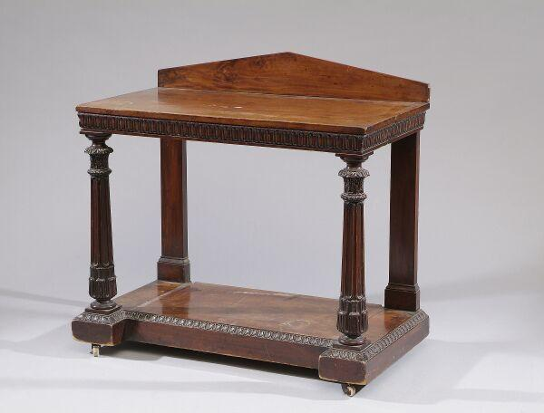 A Regency mahogany side table With lappet carved frieze on turned tapering column supports, on inverted breakfront plinth base, 97cm wide. (later mahogany top)