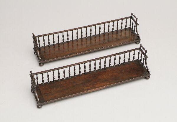 A pair of late Regency mahogany book stands With baluster turned spindle gallery back and turned carrying handles, on bun feet, 81.5cm wide. (2)