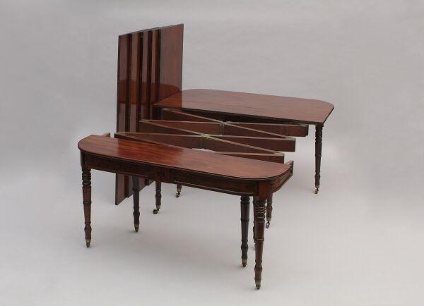 A George IV mahogany concertina action extending dining table Closing with a hinged fold-over leaf, the top with rounded corners above a panelled frieze, supported on ten ring turned legs with brass caps and castors, including five later leaves, 351 x 135cm extended (53 x 135cm closed).