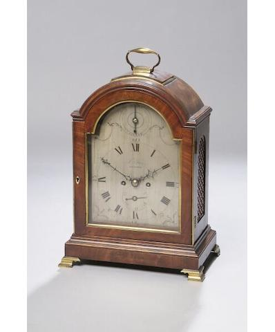 A George III mahogany bracket clock By J Farr, Bristol, and silvered arched dial and strike/silent indicator, in a case with arch top, side grilles and outset brass ogee feet, 45cm high.
