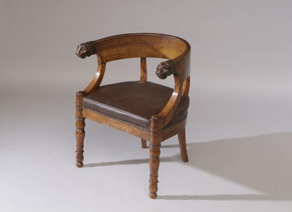 An unusual Regency or George IV mahogany tub or desk chair The deep backrail terminating in lion masks in the manner of Thomas Hope, with stuff-over seat and outset turned legs.