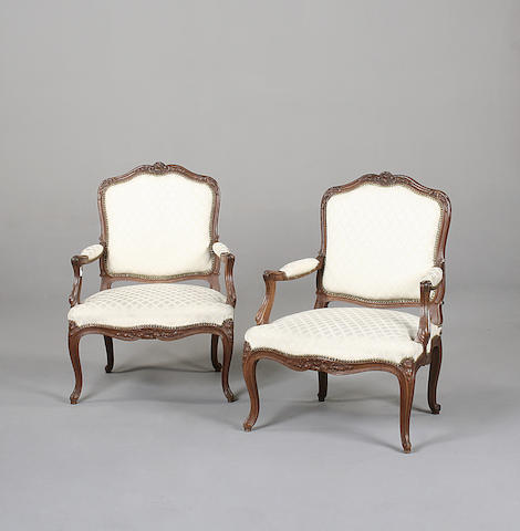 A pair of Louis XV style walnut carved fauteuil à la reine