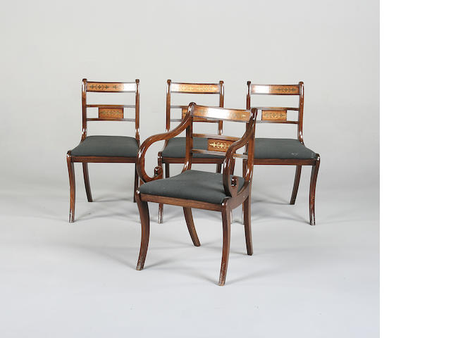 A set of four Regency style mahogany and brass inlaid dining chairs