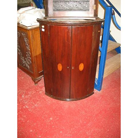 A George III mahogany bow fronted corner cabinet