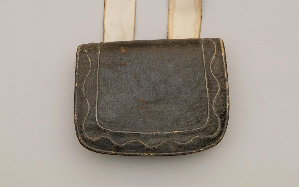 "A Most Important Late 18th Century Officers Ammunition Pouch and Belt The pouch with internal wooden rack for six cartridges, is of black leather, the flap with additional covering of black Skiver and narrow silver wire decoration, comprising two lines forming a border, and a wavy line of lace within this border, the pouch 6"" x 5"", the belt of soft white buckskin over tan skiver, this with simple iron buckle, the ends anchored to the under part of the box via sewn buckles and another returning strap, the belt 1 5/8"", the style suggests a light company officer c1780-1800, slight overall wear but otherwise very good condition for age."