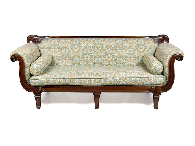 A pair of William IV carved mahogany three seater sofas