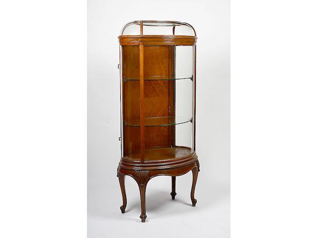 A walnut oval display cabinet,