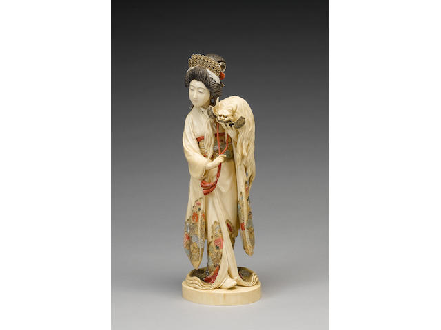 A very fine stained ivory okimono of a standing Geiko or Bijin,
