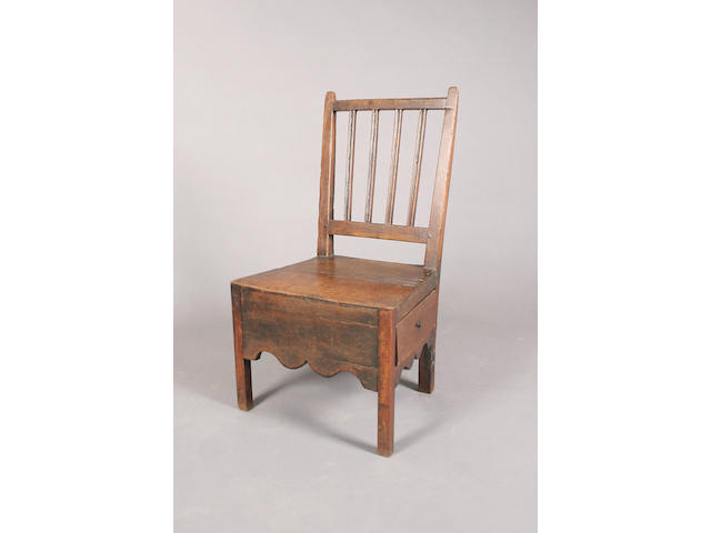 A late 18th century oak low standard chair,