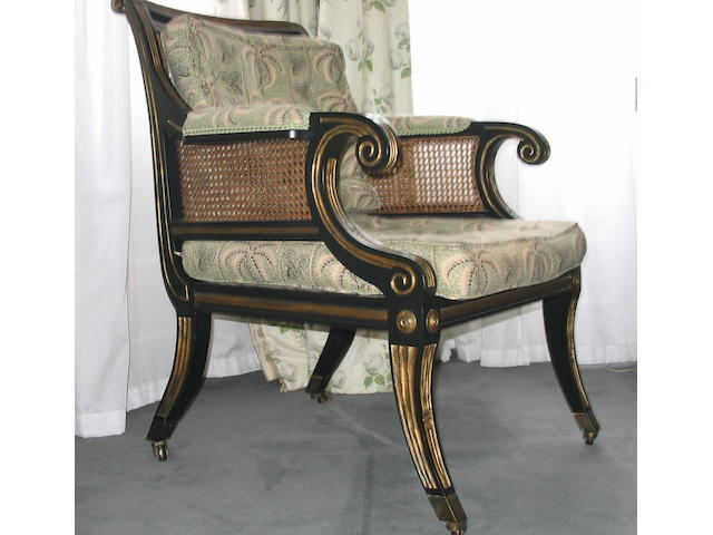 A pair of Regency style ebonised and parcel gilt bergeres