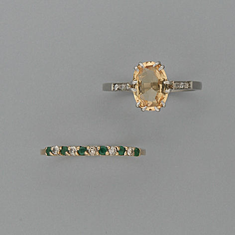 A small emerald and diamond half hoop ring