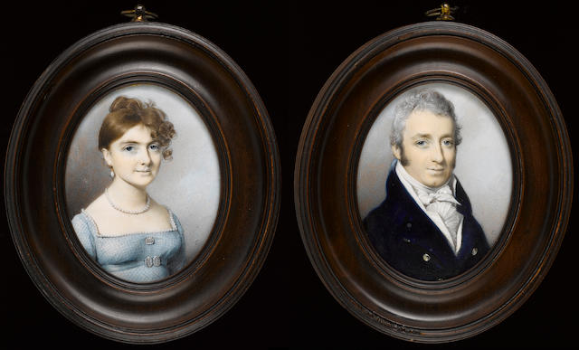 George Engleheart, A pair of portraits of a Lady and Gentleman; she wearing pale blue checked dress with white trim, blue belt with pearl buckle matching pearl brooch, necklace and drop earring, her hair upswept and falling over her face; he wearing dark blue coat, white waistcoat, frilled white chemise and tied cravat