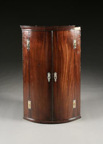 A George III mahogany bowfront hanging corner cupboard,