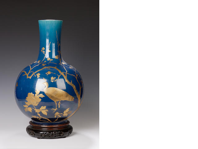 A large English aesthetic blue earthenware bottle decorated in gilt with branches and birds