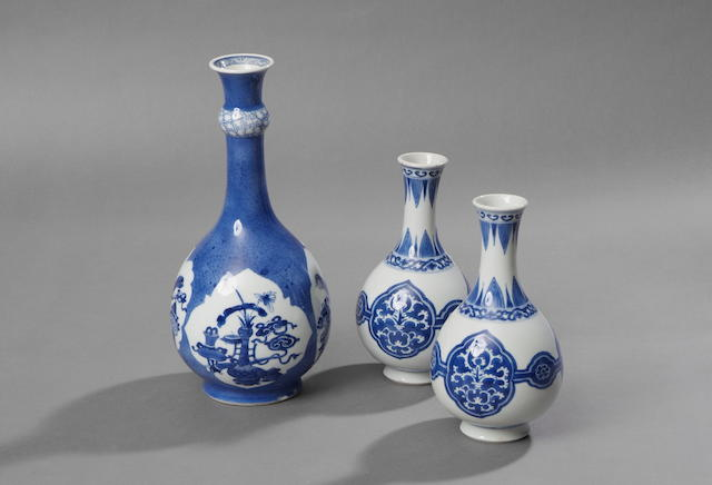A pair of Kangxi blue and white ovoid slender neck vase The sides with stylised foliate cartouche decoration, 19cm high. (2)
