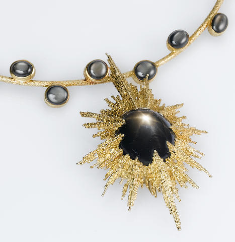 A spectacular black star sapphire pendant/necklace and pair of pendent earrings,