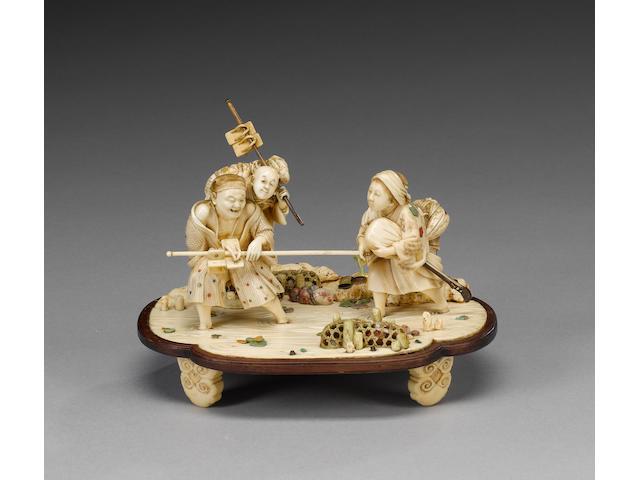 An elegant ivory okimono carved as a family