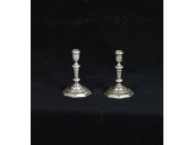A pair of silvered brass candlesticks