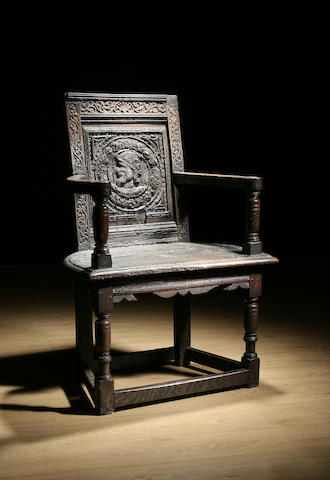A 17th Century oak caqueteuse armchair, the back carved with a man's head, lacking crest