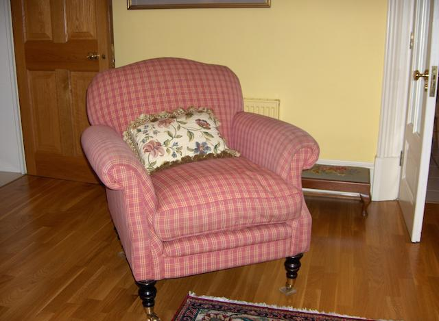 A pink checked upholstered easy armchair