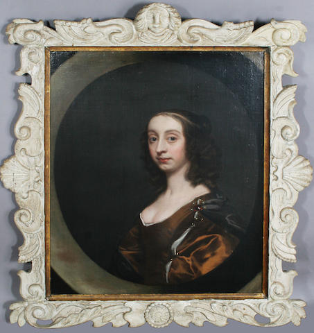 Studio of Sir Peter Leley (1618-1680)Portrait of a lady, quarter legnth, in a brown dress and grey wrap, oil on canvas, on a painted oval, in a carved wooden frame with mask cresting,