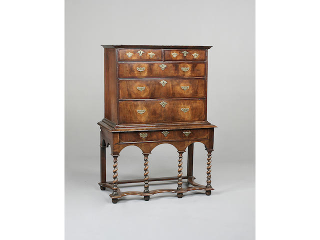 An early 18th century walnut chest on later stand