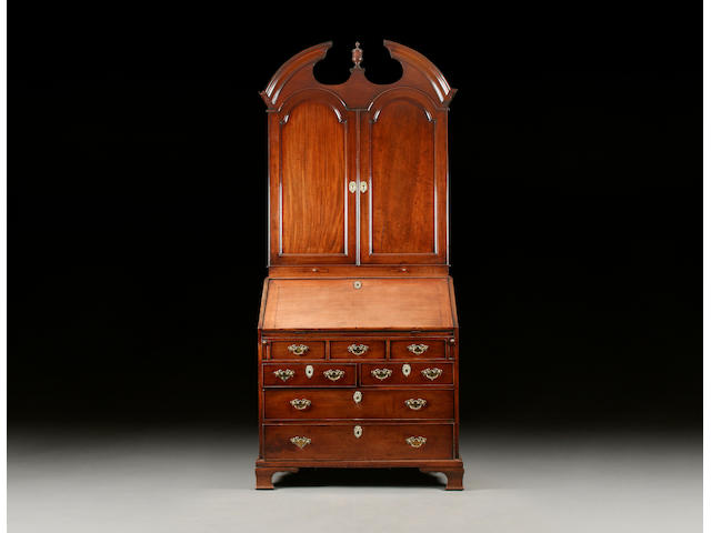 A George III mah bureau cabinet c.1760-80, with broken arch pediment, arched double doors enclosing adjustable pigeonholes and drawers, the bureau with shaped fitted interior including cupboard and bood drawers, over a well, on two short and two long cockbeaded drawers and ogee bracket feet