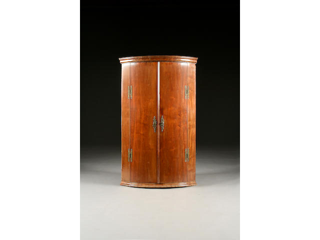 A George III mahogany bow front hanging corner cupboard