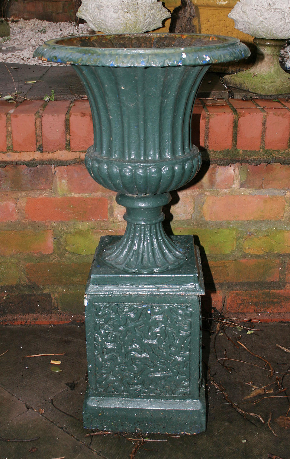 A pair of green painted cast iron terrace vases