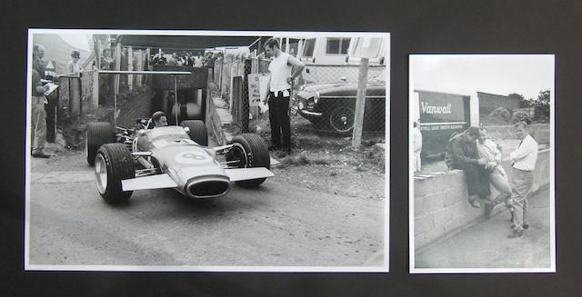A large monochrome photograph of Graham Hill at the 1968 British Grand Prix,