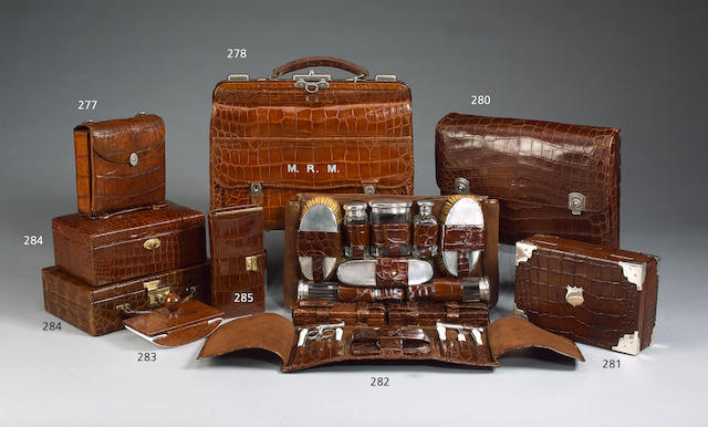 An early 20th century mid brown crocodile leather travelling sewing case and a crocodile leather cased curling tongs heater.