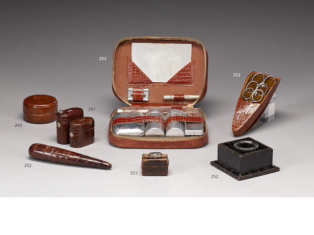 An early 20th century brown crocodile leather scissor holder, a black crocodile leather ink well, comb case, pipe, and simulated crocodile picture frame, address book, gentleman's vanity set, cigarette case, scissor holder, and oriental spectacle case (10)