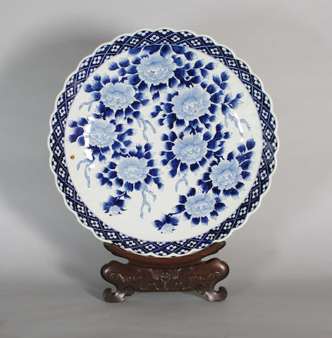 A Chinese blue and white charger and hardwood stand