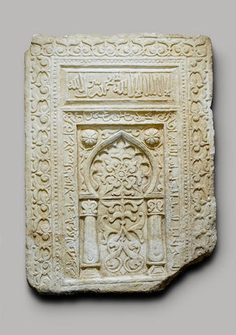 A sandstone panel depicting a mihrab arch with inscriptions