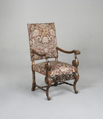A Charles II style carved mahogany open armchair