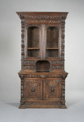A late 19th century carved oak cabinet bookcase