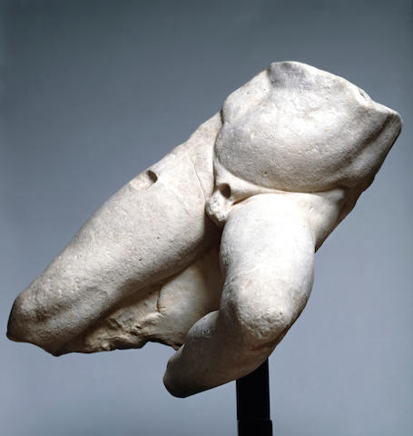 A Greek marble naked lower torso of a falling warrior