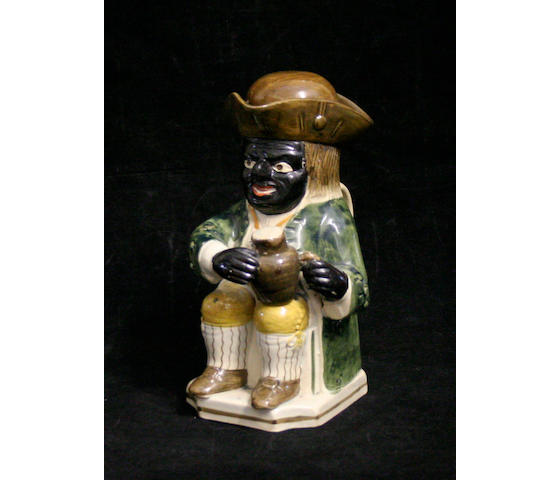 An unusual Pratt type 'black man' Toby jug and replacement cover, circa 1820-30