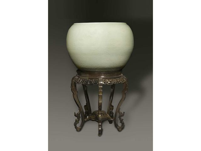 A large and very finely carved white-glazed fishbowl and stand Kangxi