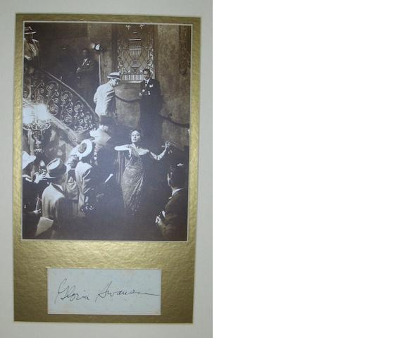 A Gloria Swanson autograph, the mounted signature inscribed on an album page