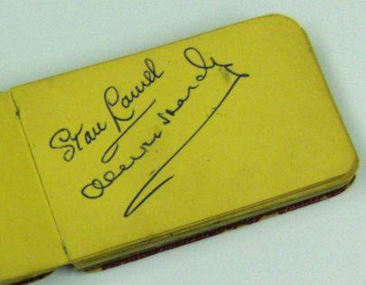 An autograph book signed by Laurel & Hardy,