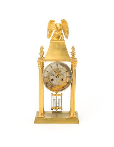 An interesting gilt brass portico clock with compound pendulum,