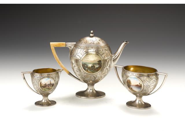 A three-piece Victorian parcel-gilt and enamel mounted pictorial tea set, by Frederick Elkington, Birmingham 1887,  (3)