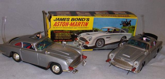 Two Gilbert James Bond tinplated Aston Martin DB5's, both battery operated,