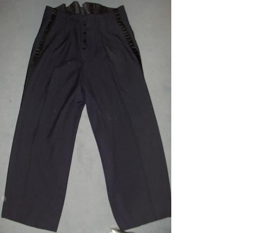 A pair of trousers worn by Oliver Hardy, of black wool,