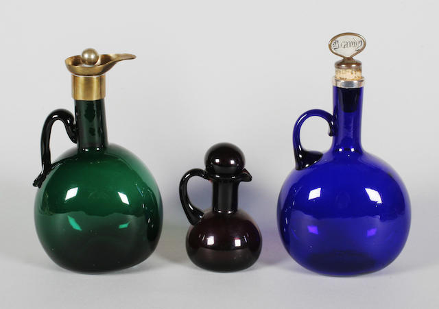 A blue glass serving bottle, a green glass serving bottle, an amethyst jug and stopper and four drinking glasses