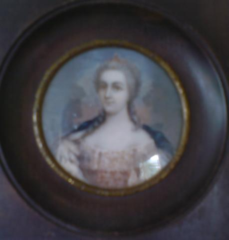 A 19th century silhouette depicting a head and shoulder portrait of a young woman with bronze highlighting, mounted within an ebonised frame, 14cm high; together with a 19th century painted ivory portrait miniature, depicting a young woman dressed in 18th century costume, 8cm diameter, (2)