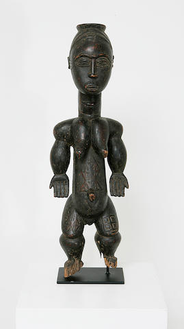 A good Bete wood ancestor figure of a standing female with an abundance of scarification and prominent breasts;